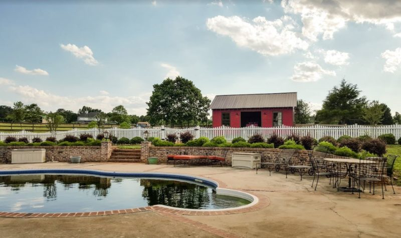 Pool behind farmhouse with red barn in distance