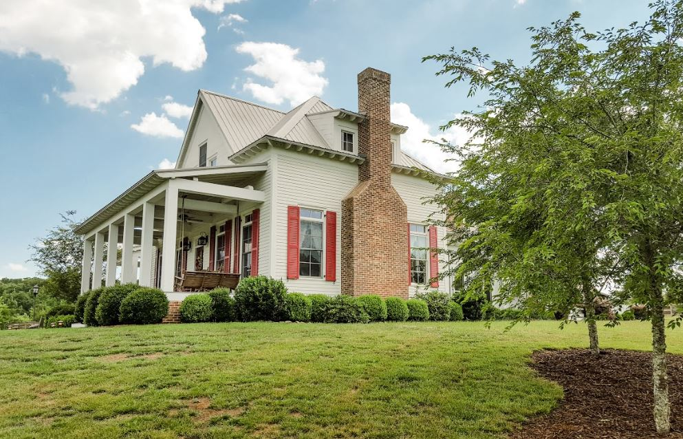 Side exterior view of the white Farmhouse with front porch and brick chimney