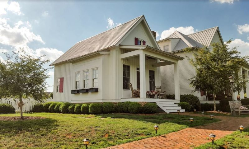 Exterior of white farmhouse with porch and red shutters