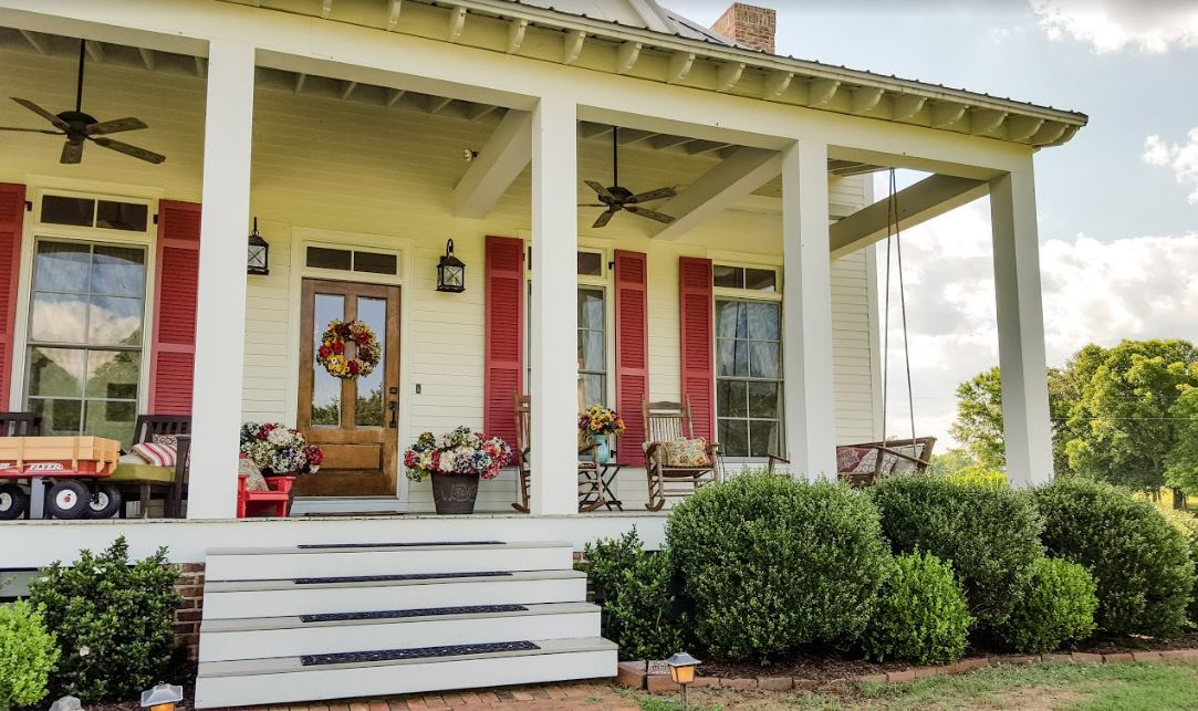 Front porch of farmhouse with white siding and red shutters