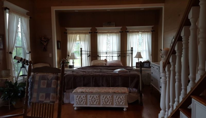 Bed in the owner\'s suite of the farmhouse with wrought iron headboard