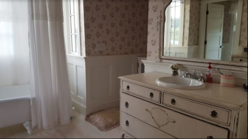 Farmhouse bathroom with antique dresser and mirror used for sink vanity