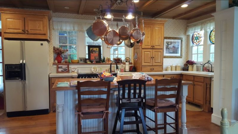 Farmhouse kitchen with barstools and copper pots hanging from pot rack over island