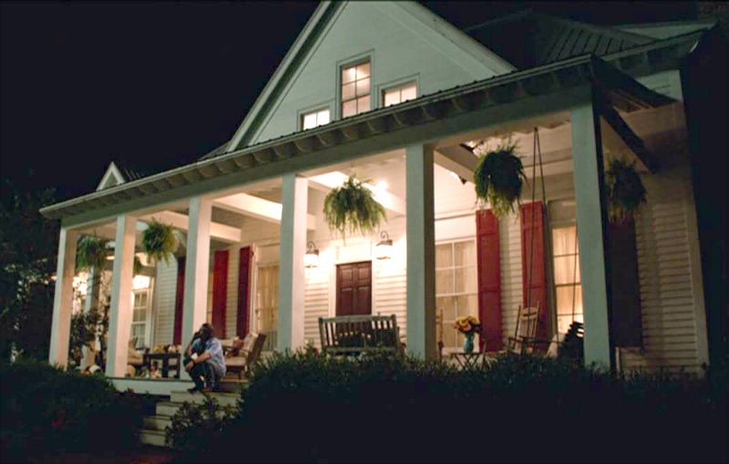 The front porch of the farmhouse in Miracles from Heaven at night with lights on