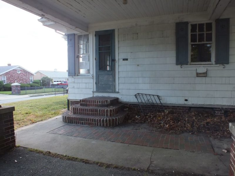 Exterior view of side door with brick steps before remodel