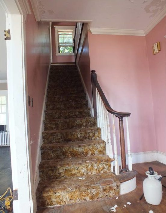 Staircase with pink walls and old carpet