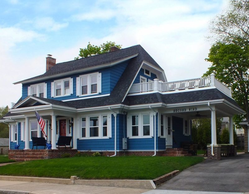 Front exterior view of newly remodeled house with blue siding and red front door