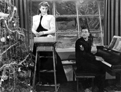 Barbara Stanwyck and Dennis Morgan by the tree in Christmas in Connecticut