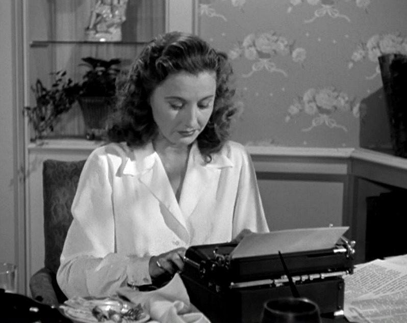 Barbara Stanwyck typing on a typewriter