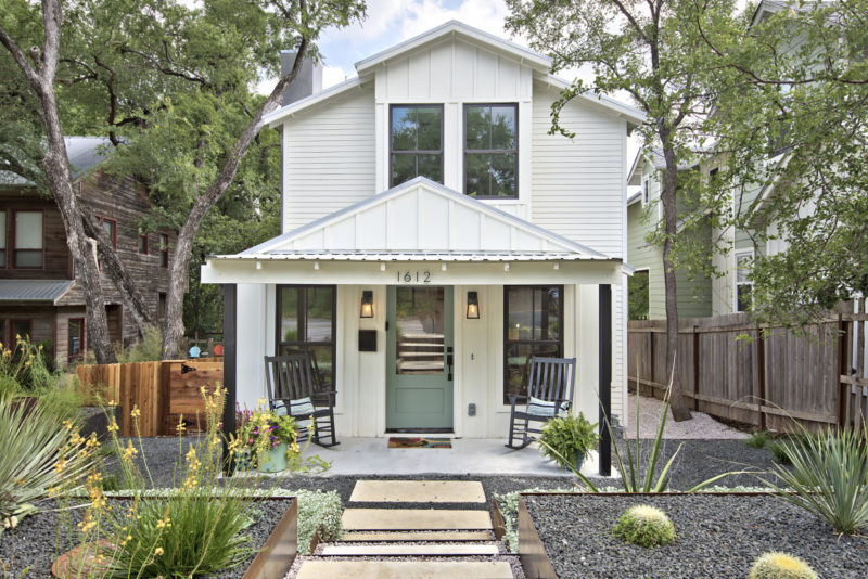 Front exterior of modern farmhouse in Austin with front porch and teal door