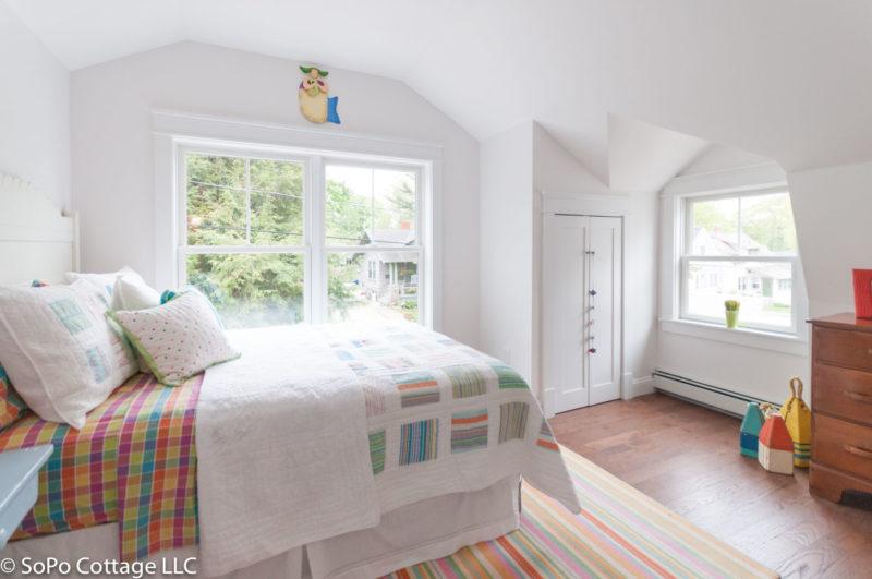 An upstairs bedroom with hardwood floor and rug