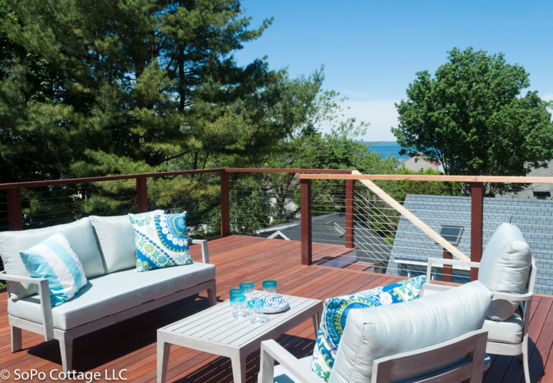 Upper deck behind house with view of the water
