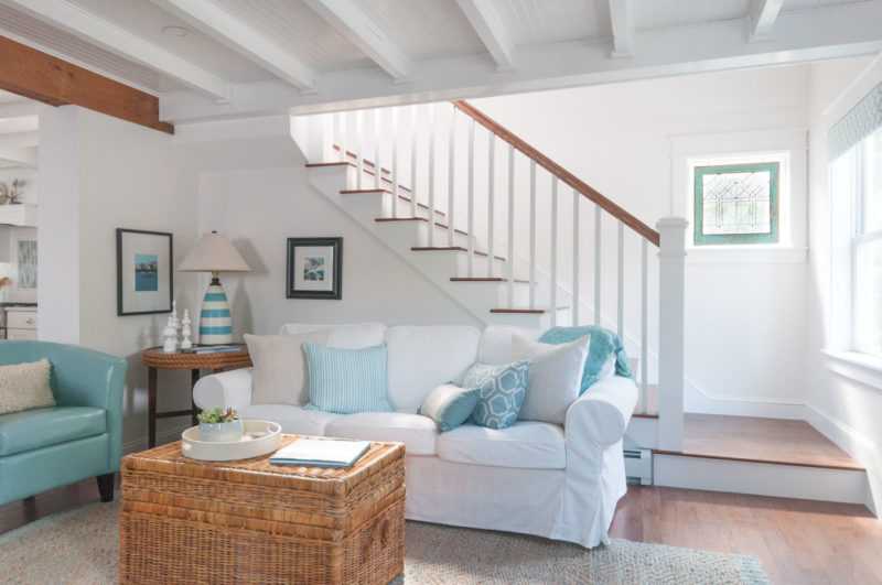 A living room with staircase and white slipcovered sofa