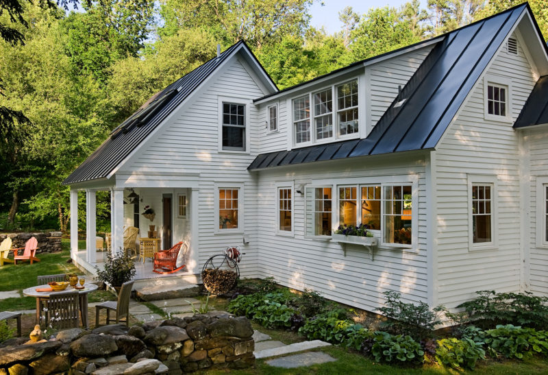 Back exterior of remodeled Cape in Vermont with white siding and back porch