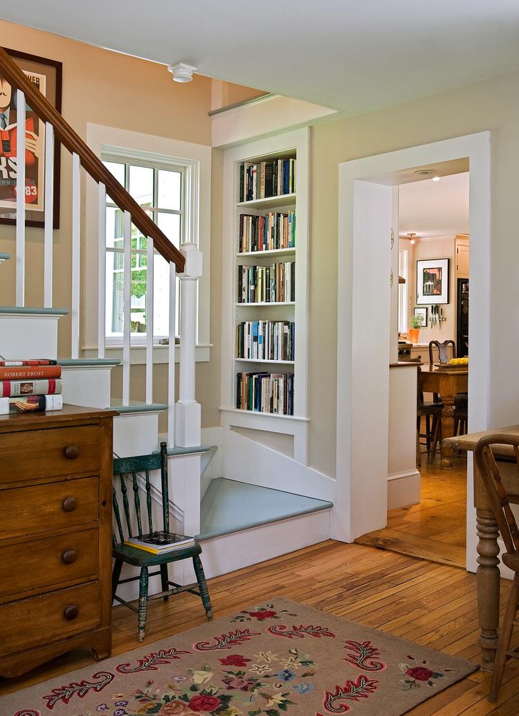 built-in bookshelves at bottom of staircase landing