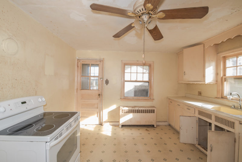 A kitchen with a stove top oven sitting next to a window before remodel