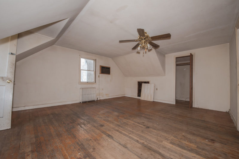 A large empty room with a wood floor before remodel