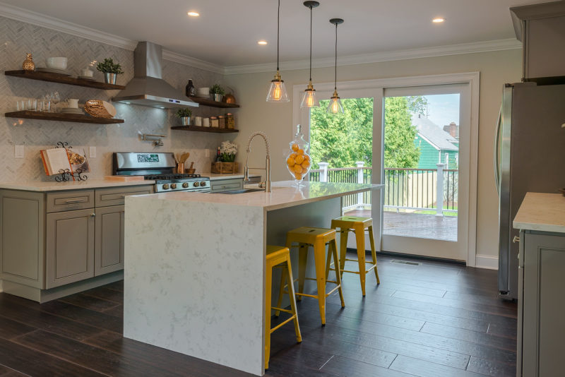 A kitchen with an island and yellow barstools