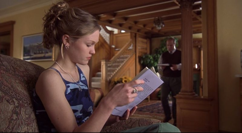 Julia Stiles reading a book in the living room