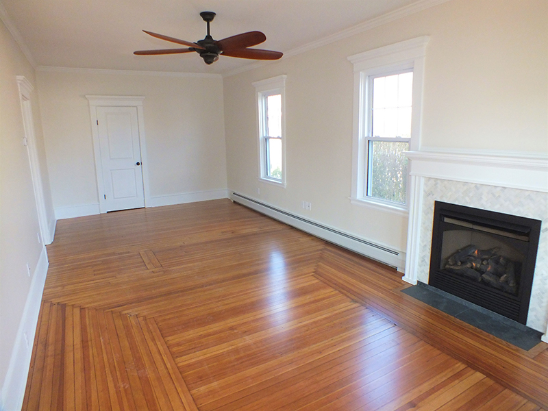 A living room with a hardwood floor and fireplace after remodel