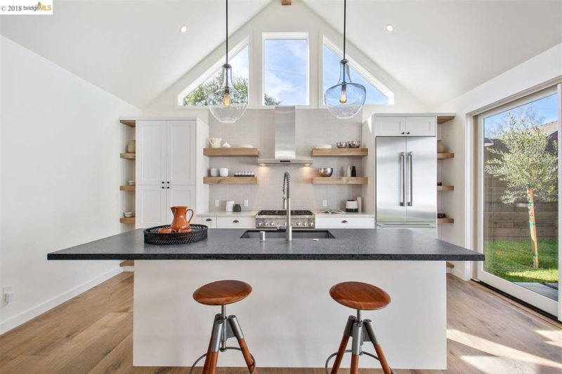 White kitchen with vaulted ceiling and island