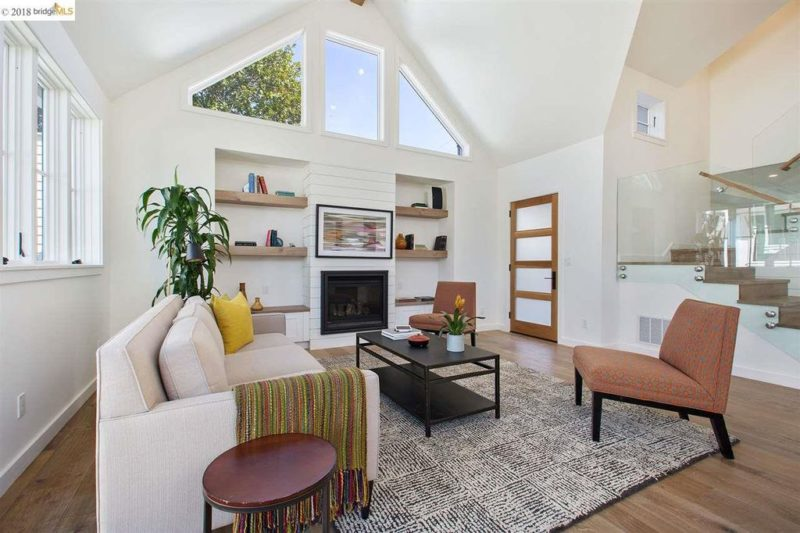A living room with fireplace and built-in shelves on either side