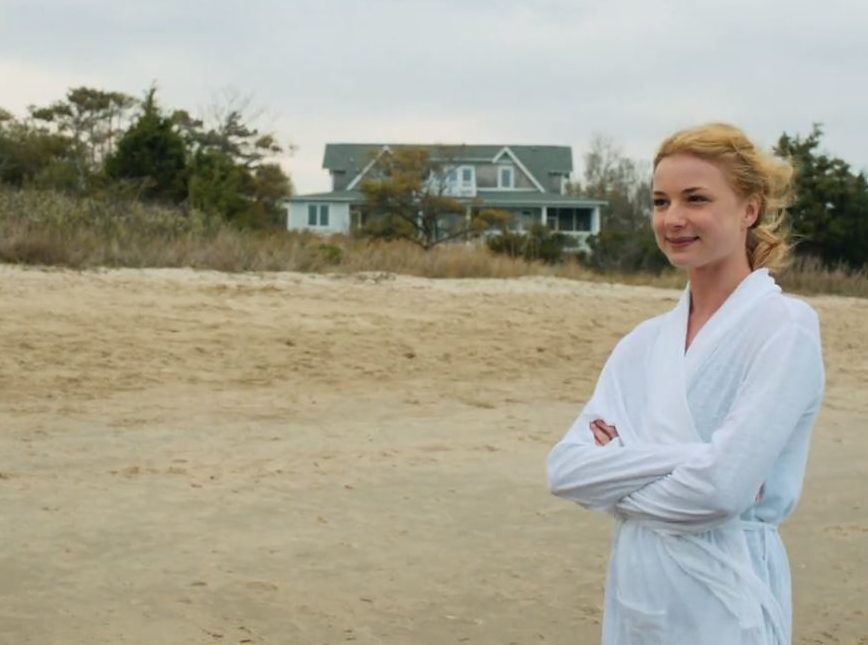 Emily Thorne standing on sandy beach in front of house
