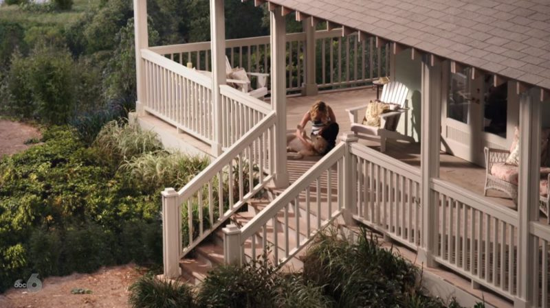 Emily Thorne on front porch of beach house with dog