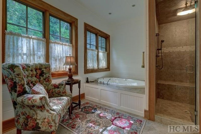Bathroom with upholstered armchair and tub