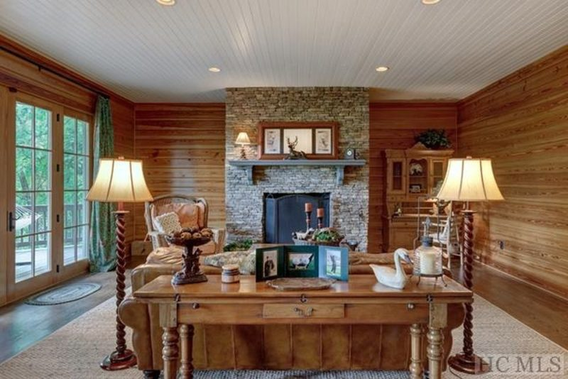 Lower level family room with wood plank walls and stone fireplace