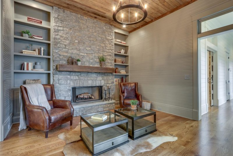 A living room with stone fireplace and two leather chairs
