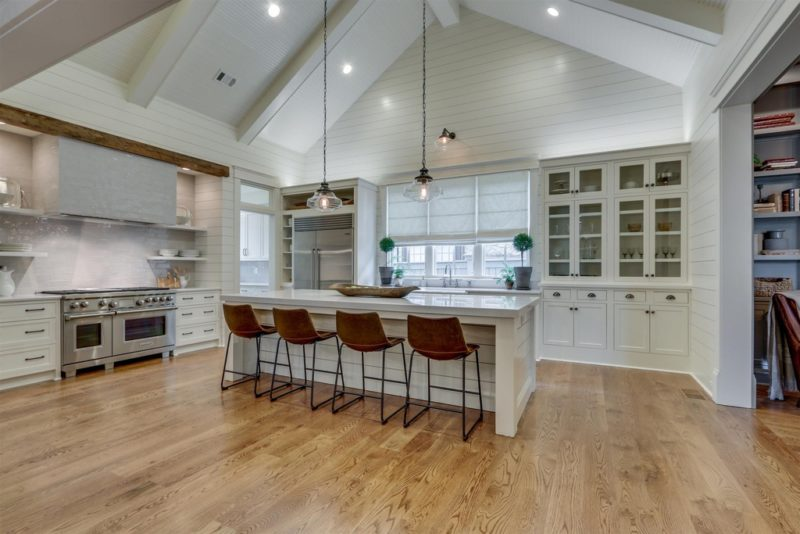 A kitchen with a hard wood floor, vaulted ceiling, and white cabinets