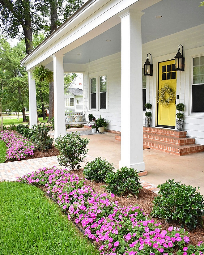 White Cottage with Yellow Door Front Porch