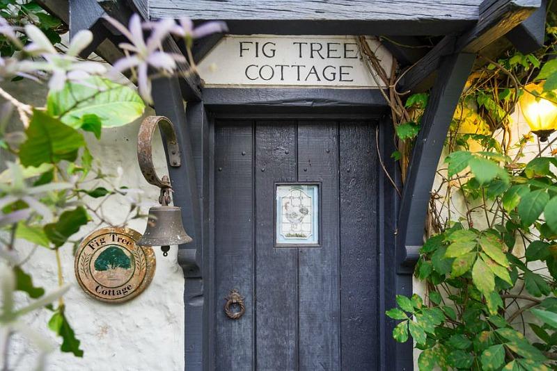 Front door of cottage with sign Fig Tree Cottage above door