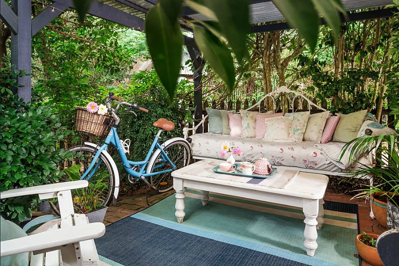 Blue bike with basket and settee in backyard