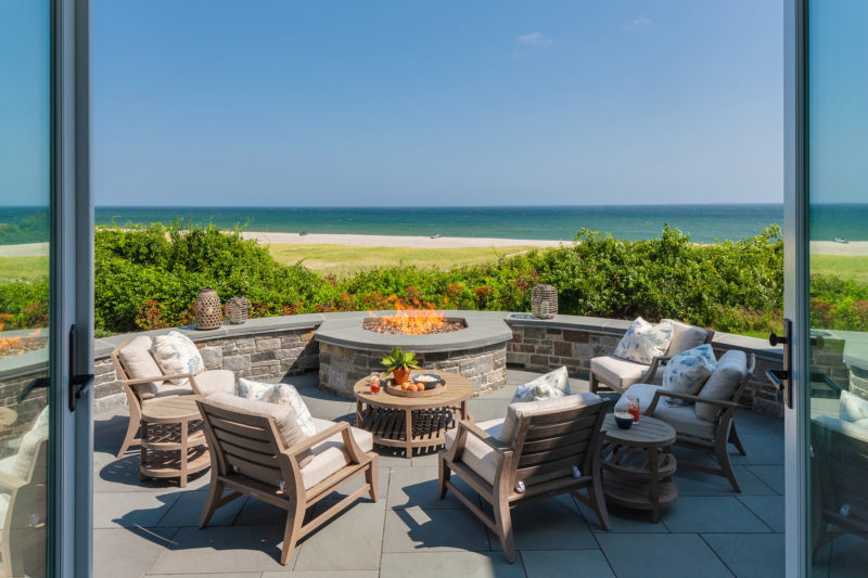 A view of a beach from a fire pit with chairs