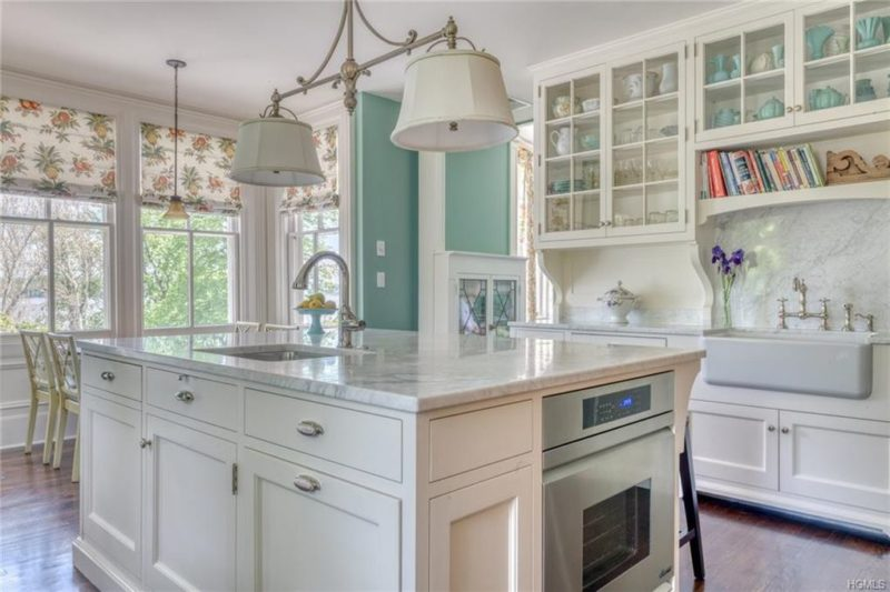 A kitchen with a large white island, marble countertop, and sink
