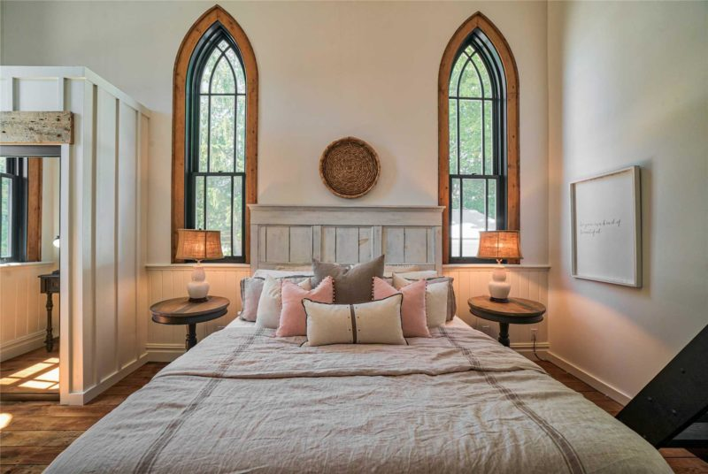 Bed between two tall windows in converted church