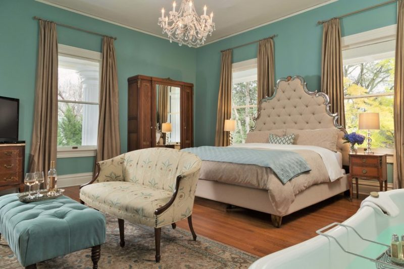 Bedroom with teal walls and chandelier