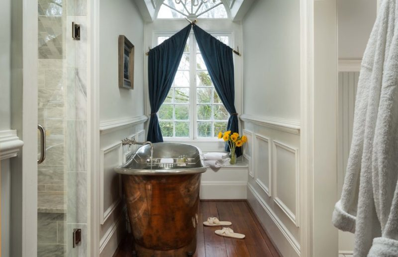 Freestanding copper tub in bathroom with wood floor