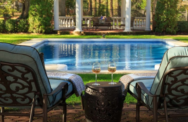A couple of lawn chairs beside the pool with wine glasses