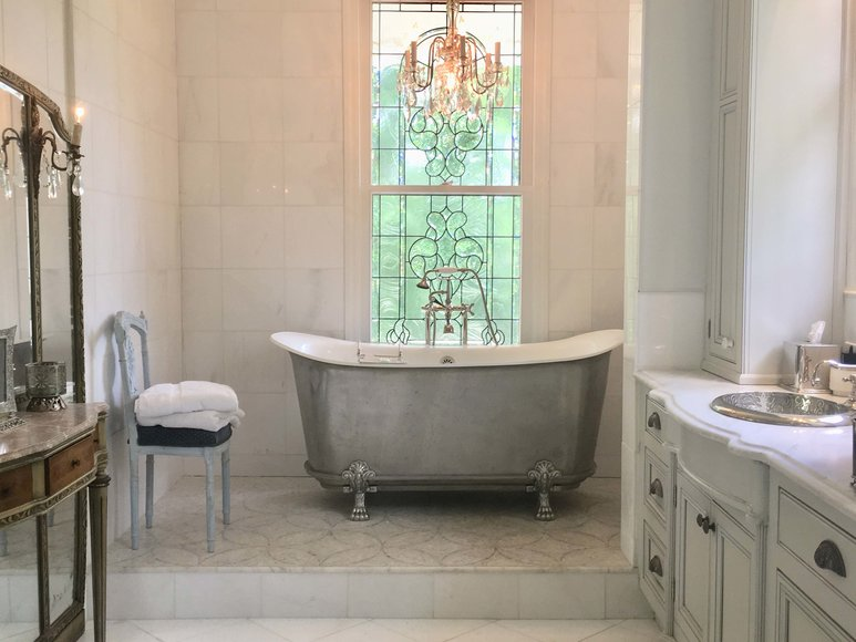 Freestanding tub in front of window with chandelier