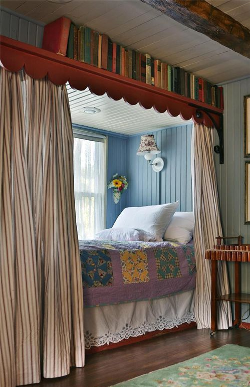 Built-in bed with privacy curtains and blue-painted paneling