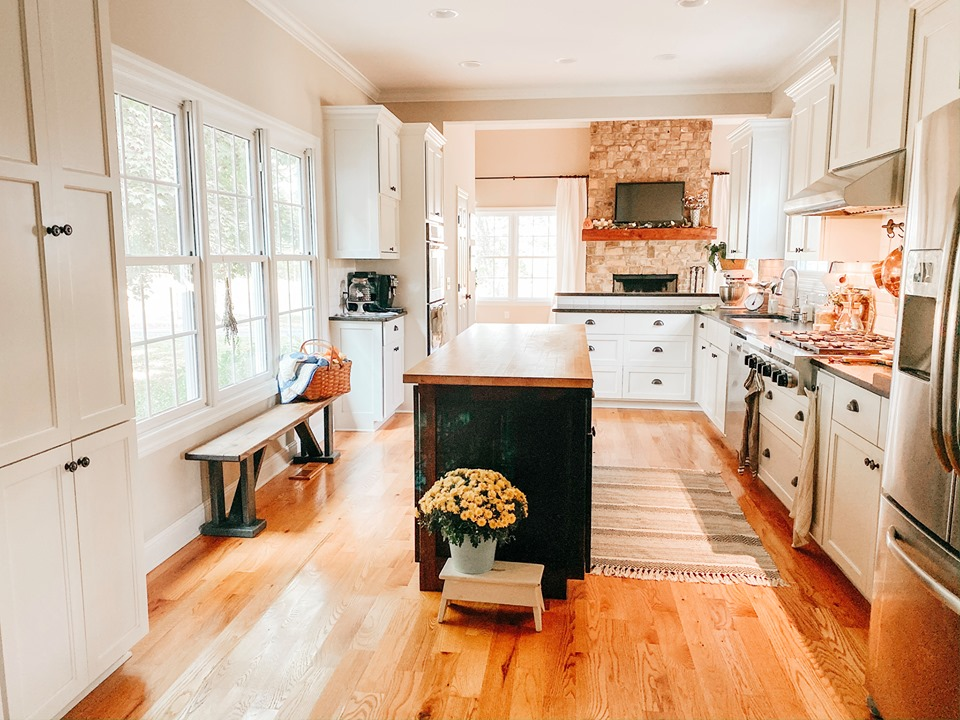 A kitchen with a wood floor and black island