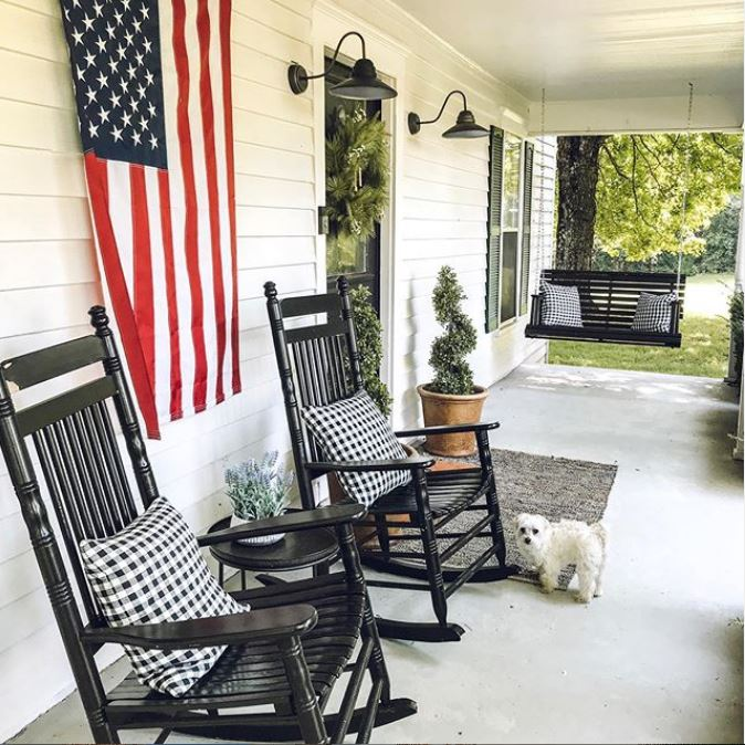 Front porch with flag, rocking chairs and swing