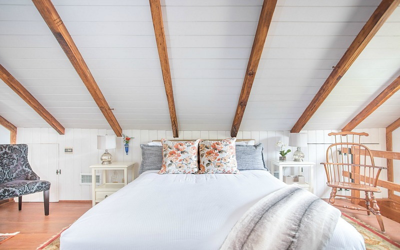 Bed in bedroom with beamed ceiling