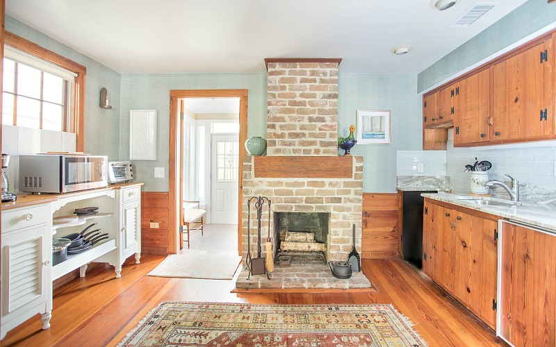 A kitchen with wooden cabinets and a fireplace