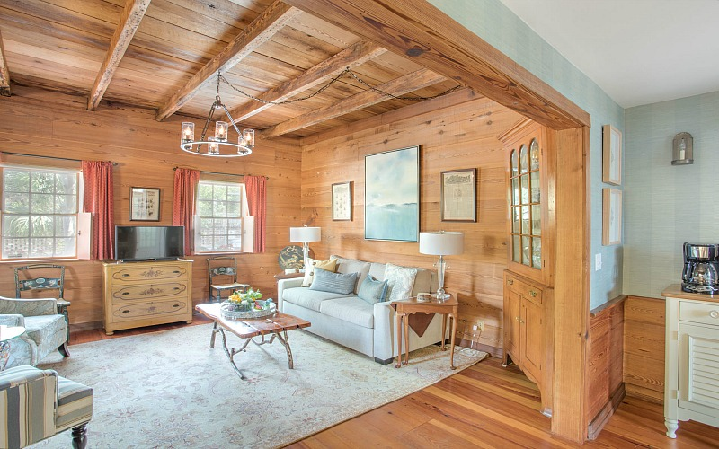 Freeman\'s Cottage living room with wood-plank walls and sofa