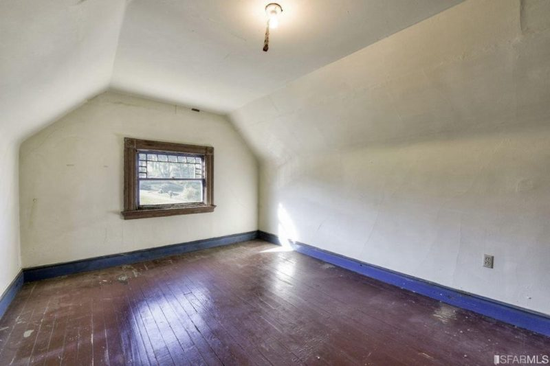 Empty attic room with window at top of house