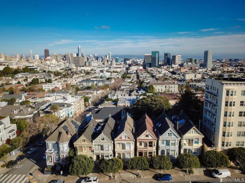 Aerial view of painted Victorians on Steiner with San Francisco in background